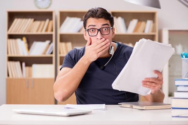 Erschrockener student mit schreibarbeit in der bibliothek Premium Fotos