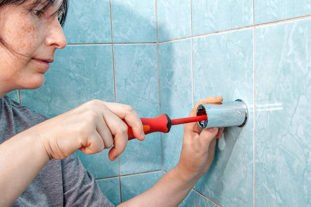 Ersetzen der sanitärinstallation im badezimmer, frau mit schraubendreher an der wandhalterung zum duschen befestigt. Premium Fotos