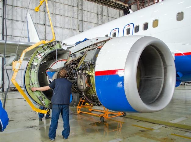 Ersetzen sie den motor im flugzeug, tippen arbeitende menschen. konzeptwartung von flugzeugen. Premium Fotos