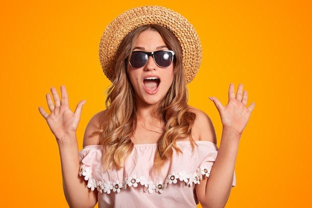 Erstaunlich schöne junge europäische frau in sommerhut, trendige sonnenbrille und modische bluse, umklammert hände Premium Fotos