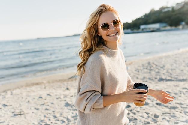 Erstaunliche blinde frau, die tasse kaffee im strand hält. enthusiastisches weibliches modell in der sonnenbrille, die nahe see am kalten tag aufwirft. Kostenlose Fotos