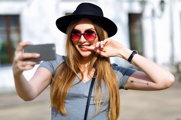 Erstaunliche blonde frau, die selfie auf der straße macht Kostenlose Fotos