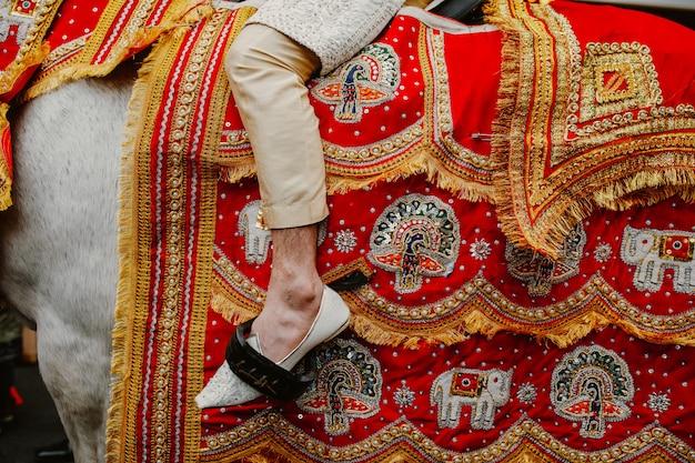 Erstaunliche details der pferdedecke und des beines des mannes Kostenlose Fotos