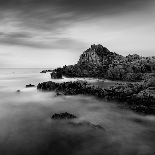 Erstaunliche graustufenaufnahme eines felsigen strandes in guernsey nahe dem fort houmet Kostenlose Fotos