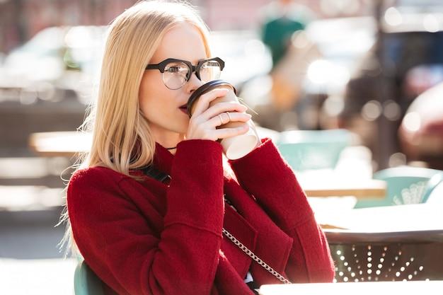 Erstaunliche junge kaukasische frau, die per telefon kaffee trinkt Kostenlose Fotos