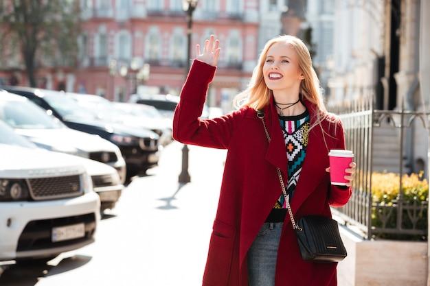 Erstaunliche mode junge blonde frau winken und kaffee trinken. Kostenlose Fotos