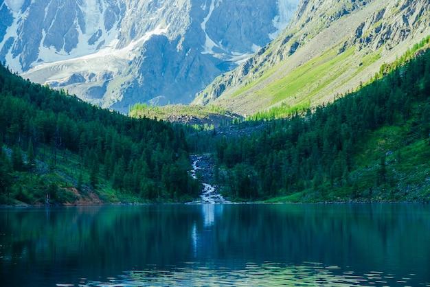 Erstaunlicher bach vom gletscher fließt in see. schatten der berge am wald. Premium Fotos