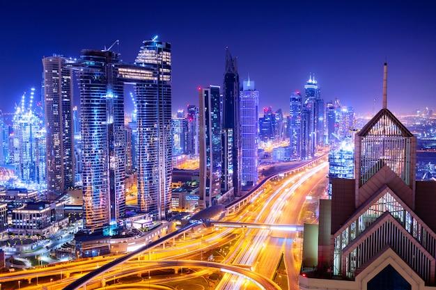 Erstaunliches skyline-stadtbild mit beleuchteten wolkenkratzern. innenstadt von dubai bei nacht, vereinigte arabische emirate. Premium Fotos