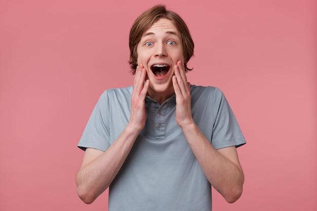 Erstaunt aufgeregter junger mann, der sein gesicht berührt, kann nicht an sein glück glauben, mit langen, ordentlich gekämmten haaren und zahnspangen trägt er ein polo-t-shirt und fühlt sich glücklich überrascht, isoliert über der rosa wand Kostenlose Fotos