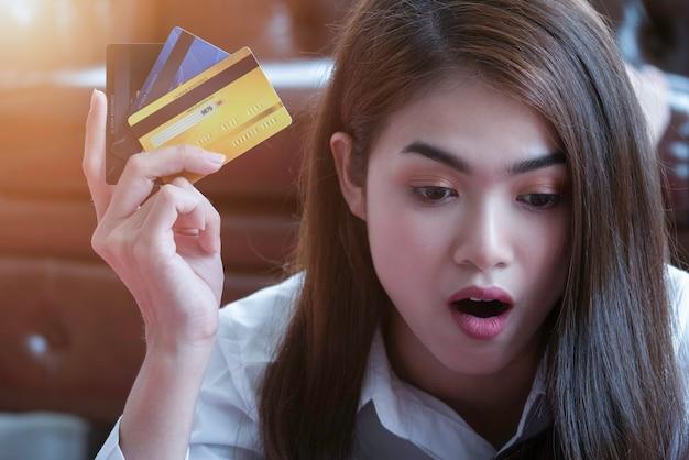 Erstaunte frau, die online zu hause mit kreditkarte im wohnzimmer kauft Premium Fotos