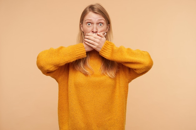 Erstaunte junge hübsche rothaarige frau mit lässiger frisur, die ihren mund mit erhobenen händen kegelt, während sie benommen schaut und auf beige steht Kostenlose Fotos