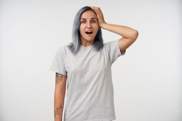 Erstaunte junge hübsche tätowierte frau mit kurzen blauen