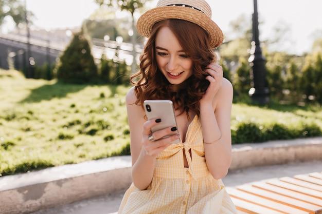 Erstaunte junge ingwerfrau las telefonische nachricht im park. außenporträt des reizenden eleganten mädchens im gelben kleid, das auf bank mit smartphone sitzt. Kostenlose Fotos