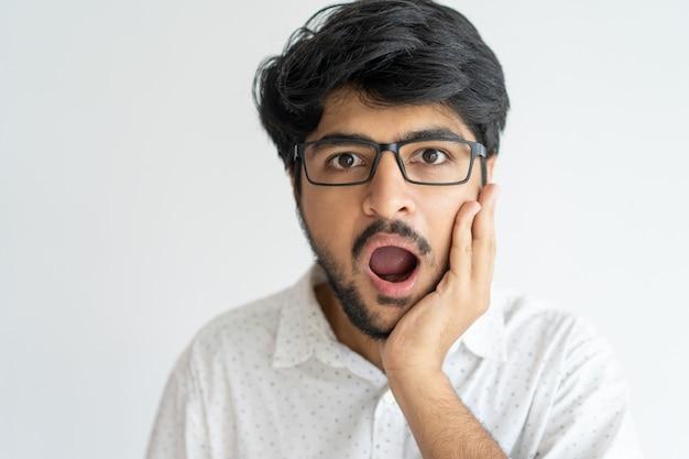 Erstaunter ausdrucksvoller junger mann mit dem offenen mund, der hand auf backe hält Kostenlose Fotos