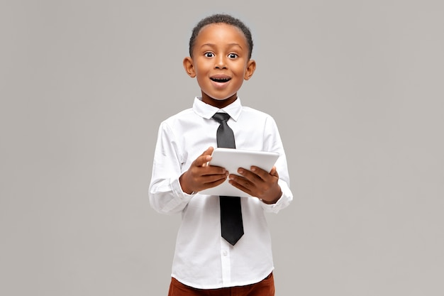 Erstaunter dunkelhäutiger kleiner junge, der weißes hemd und schwarze krawatte trägt, die drahtlose hochgeschwindigkeits-internetverbindung auf digitalem tablett genießt, erstaunten blick überrascht und zeichentrickfilm online anschaut Kostenlose Fotos