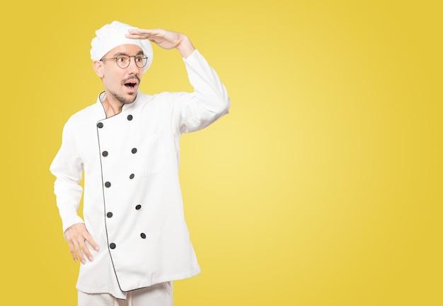 Erstaunter junger koch mit einer geste des wegschauens Premium Fotos