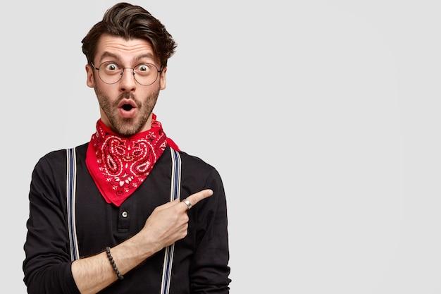 Erstaunter stylischer hipster hat einen trendigen haarschnitt, öffnet den mund mit überraschung und ist nicht bereit, für diesen artikel zu werben Kostenlose Fotos