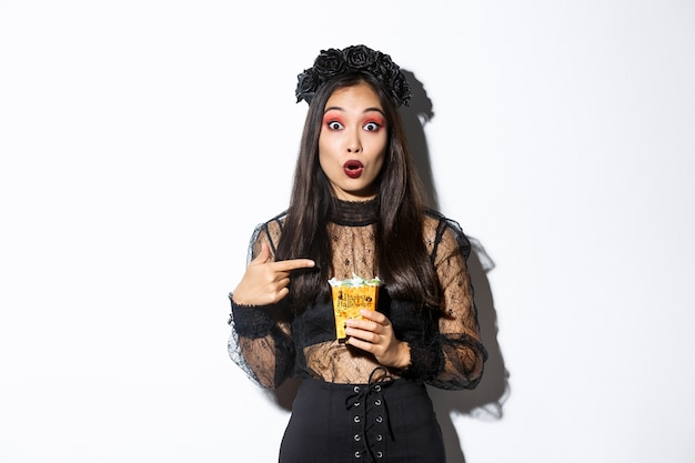 Erstauntes asiatisches mädchen, das kamera betrachtet, während finger auf süßigkeiten zeigt Kostenlose Fotos