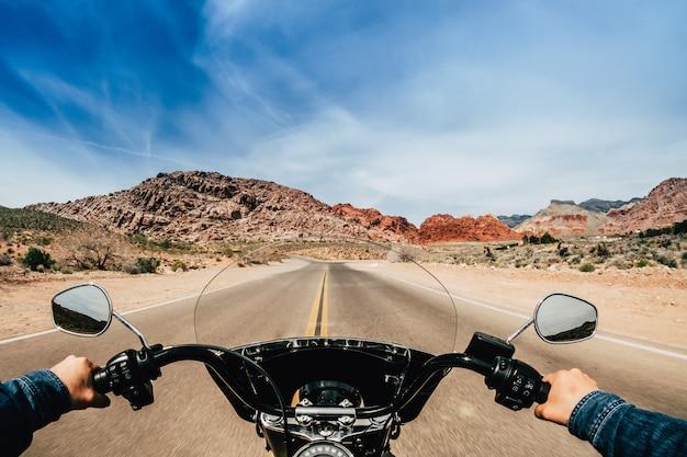 Erste personenansicht eines mannes, der ein motorrad auf einer straße fährt Premium Fotos