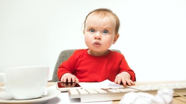 Erste sms. kindbaby, das mit tastatur des modernen computers oder des laptops in weiß sitzt Kostenlose Fotos