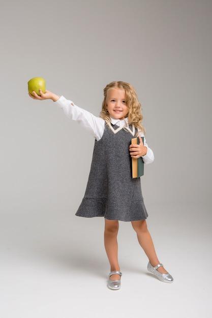 Erstklässler mit büchern und einem apple, der auf einem hellen hintergrund lächelt Premium Fotos