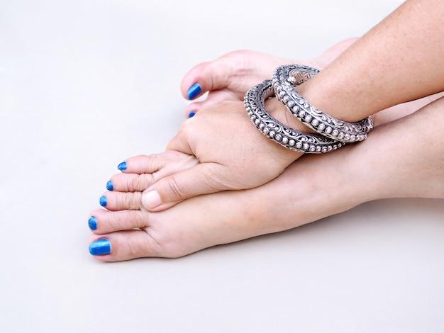Erwachsene asiatin mit den blauen zehennägeln und abnutzungsgewinn auf handgelenk, verwenden handmassage auf füßen, um sich zu entspannen. Premium Fotos