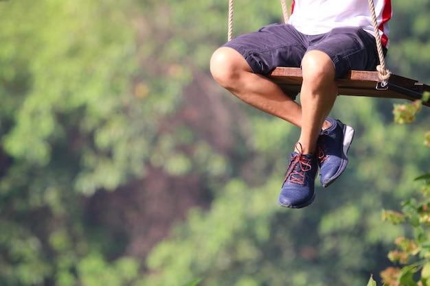 Erwachsene beine, die auf der schwingeneinsamkeit spielt im park spielerisch und glücklich den äußeren hintergrund sitzen Premium Fotos
