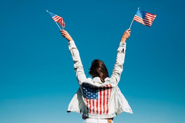 Erwachsene frau, die hände mit amerikanischen flaggen anhebt Kostenlose Fotos