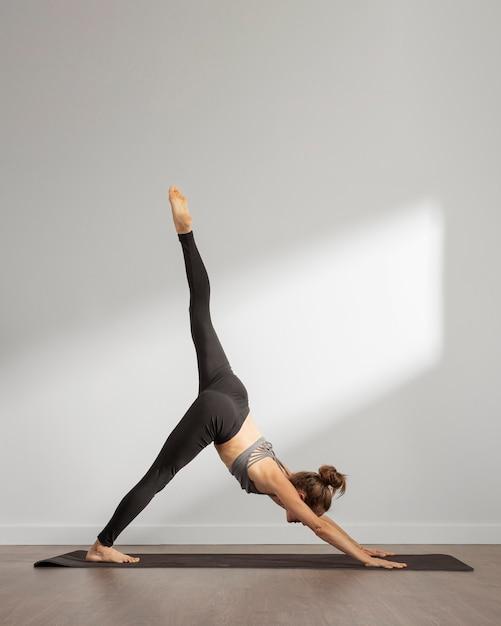 Erwachsene frau, die yoga zu hause macht Kostenlose Fotos
