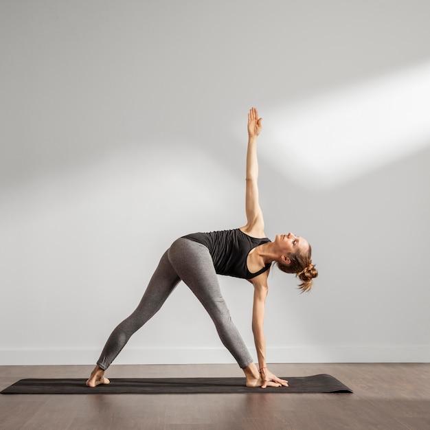 Erwachsene frau, die yoga zu hause macht Premium Fotos