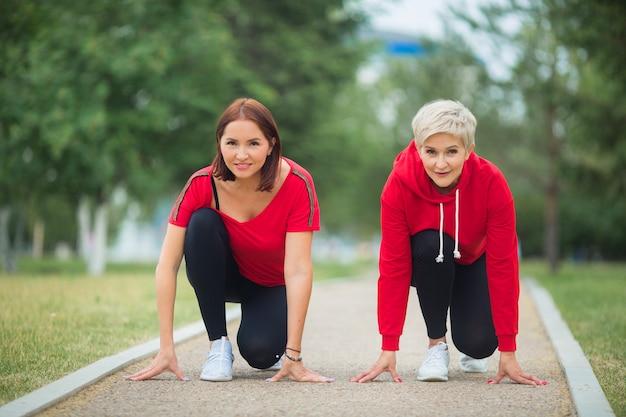 Erwachsene frauen in sportbekleidung, die sich auf das joggen im park vorbereiten Premium Fotos