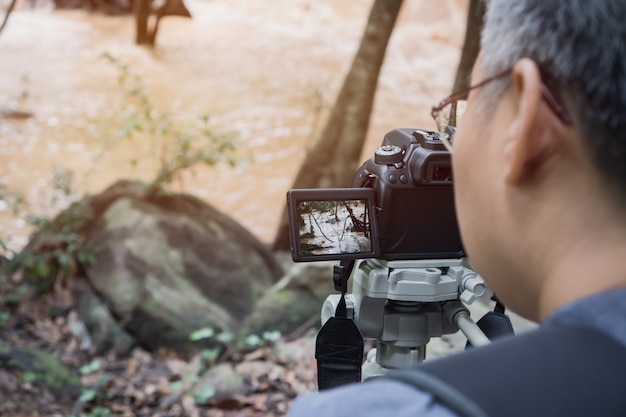 Erwachsene leute videojournalist oder reporter nehmen foto oder video bei stream river schnelle landschaft Premium Fotos