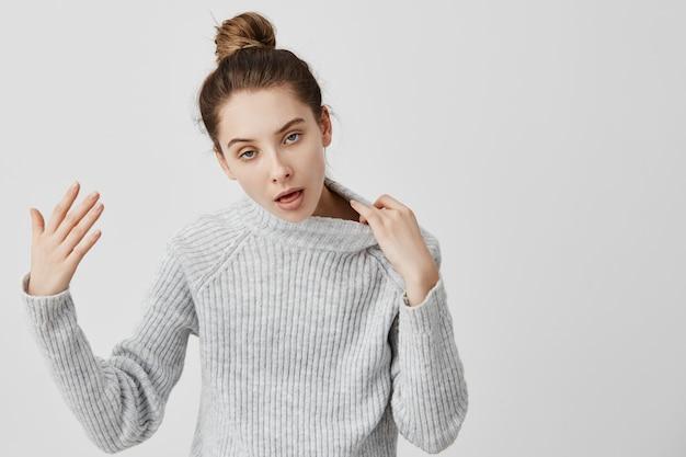 Erwachsene mädchen 20s mit hitzschlag gestikulieren sie braucht frische luft. frau mit dem haar im brötchen, das warme kleidung trägt, die heißes öffnen des mundes für atem fühlt. körpersprache Kostenlose Fotos