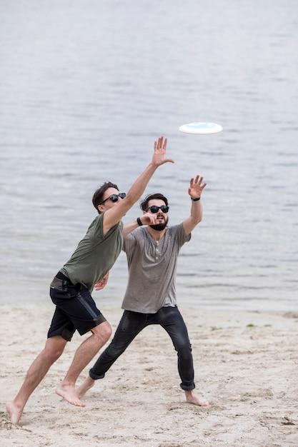 Erwachsene männer, die auf strand für anziehenden frisbee laufen Kostenlose Fotos