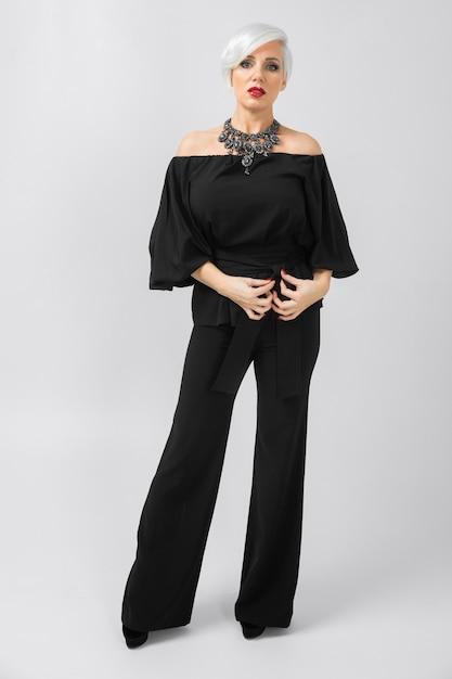 Erwachsene schöne überzeugte moderne geschäftsfrau in der losen kleidung, die auf grauem t-shirt besitzt Premium Fotos