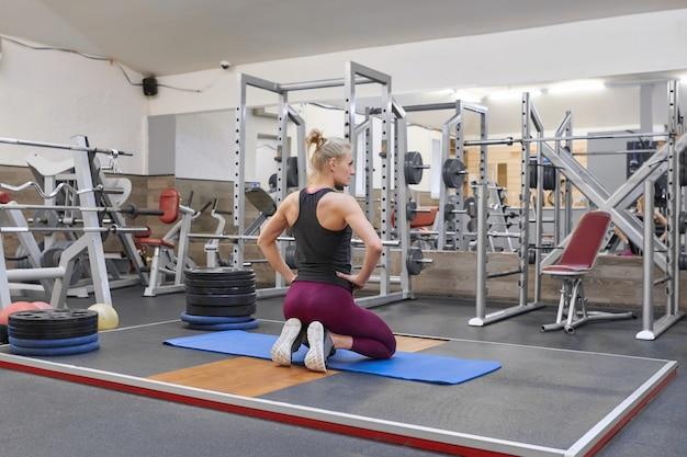 Erwachsene schöne weibliche blondine, die übendes yoga ausdehnend tut Premium Fotos