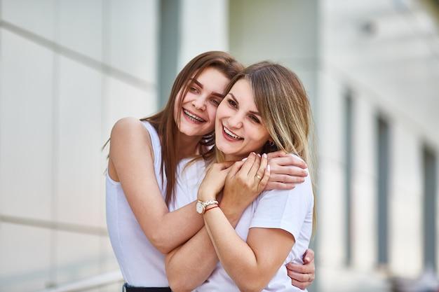 Erwachsene tochter umarmt mutter und beide lächeln in die kamera. Premium Fotos
