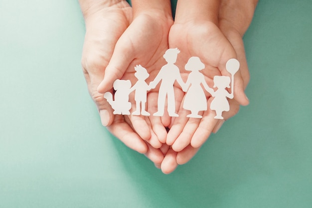 Erwachsene und kinder hände halten papier familienausschnitt, familienheim, adoption, pflege. Premium Fotos