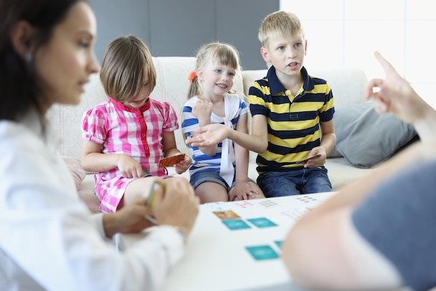 Erwachsene und kinder sitzen an einem tisch, an dem sich spielkarten befinden. der junge argumentiert und bespricht die regeln mit einem erwachsenen. Premium Fotos