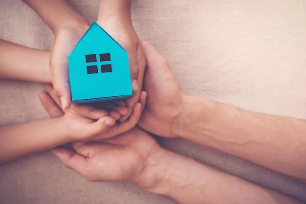 Erwachsene und kinderhände, die haus des blauen papiers für familienheim und obdachlosenheimkonzept halten Premium Fotos