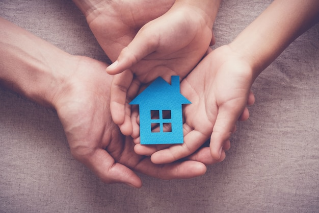 Erwachsene und kinderhände, die papierhaus, familienhaus und obdachloses schutzkonzept halten Premium Fotos