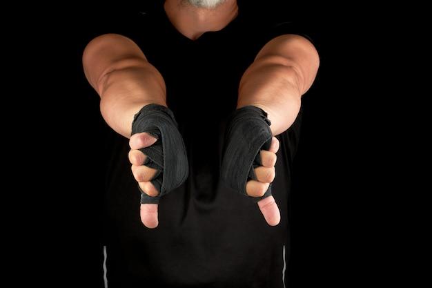 Erwachsener athlet in der schwarzen uniform und in den händen zurückgewickelt mit textilverband Premium Fotos