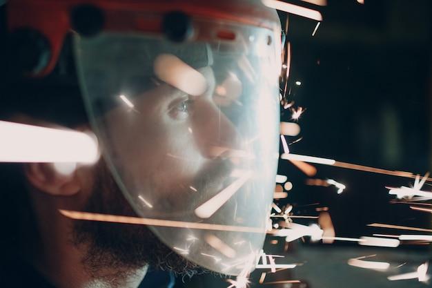 Erwachsener bärtiger mann in transparenter schutzmaske mit fliegenden metallpartikeln funken in der dunkelheit Premium Fotos