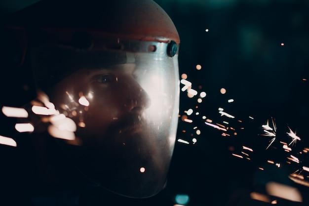 Erwachsener bärtiger mann in transparenter schutzmaske und schleifersäge mit fliegenden metallpartikeln funken in der dunkelheit Premium Fotos