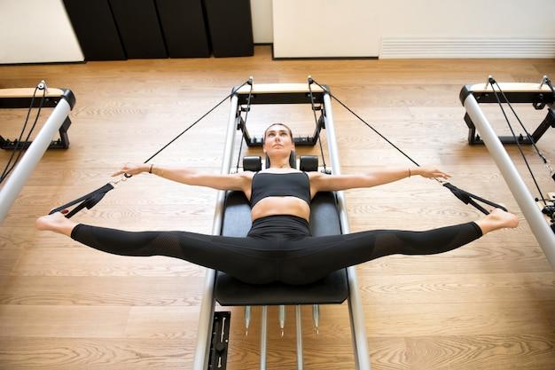 Erwachsener, der pilates maschine verwendet, um beine auszudehnen Premium Fotos