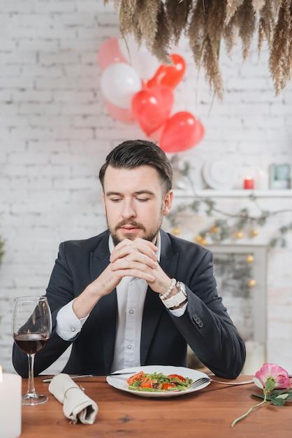 Erwachsener einsamer mann am tisch mit romantischem abendessen Kostenlose Fotos