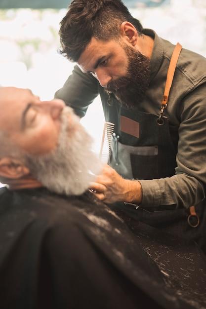 Erwachsener friseur, der kundenbart am friseursalon rasiert Kostenlose Fotos