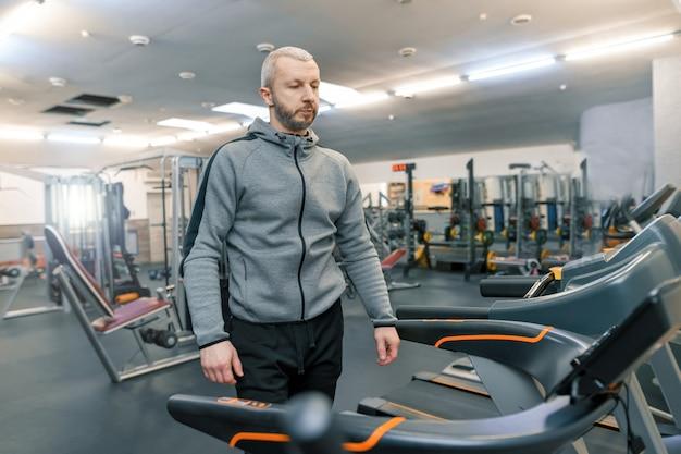 Erwachsener hübscher bärtiger mann, der körperliche übungen tut Premium Fotos