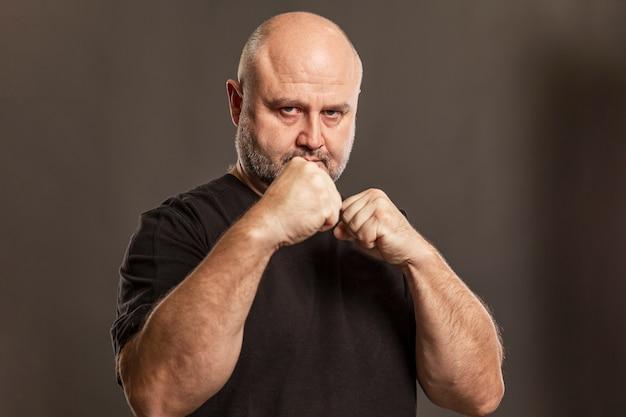 Erwachsener kahler mann in einer kampfhaltung. Premium Fotos