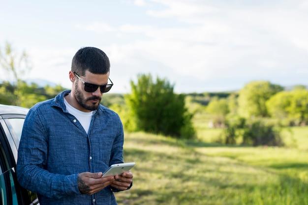 Erwachsener mann, der auf auto sich lehnt und tablette verwendet Kostenlose Fotos